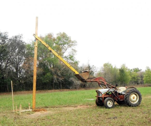 Pole barn with an 8N truss boom setting a pole